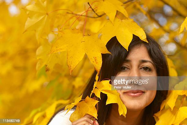 Woman looking through leaves in autumn