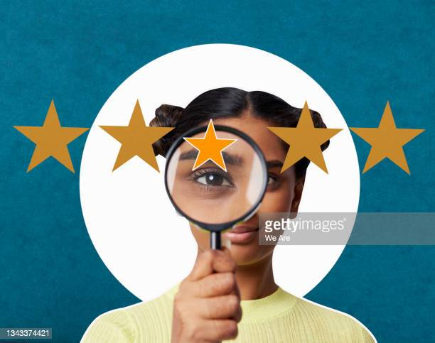 woman looking through magnifying glass at 5 stars - only young women stock pictures, royalty-free photos & images