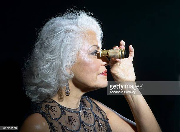 woman looking through opera glasses, profile - earring stock pictures, royalty-free photos & images