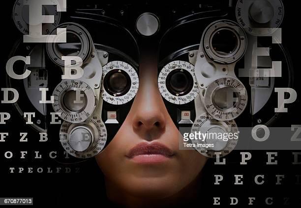 Woman looking through phoropter