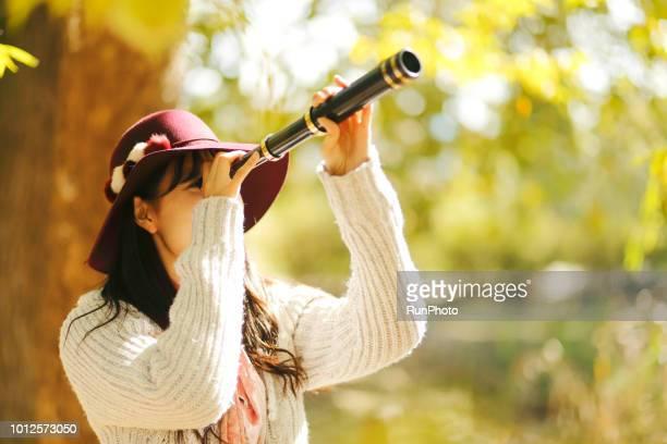 Woman looking through telescope in autumn park