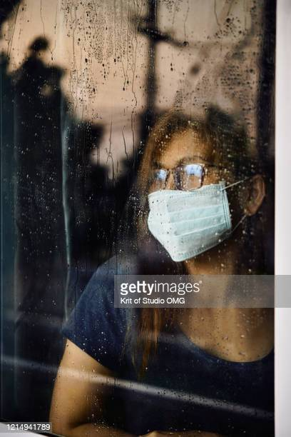 woman looking through the wet window during stay home while covid-19  back - lockdown - fotografias e filmes do acervo