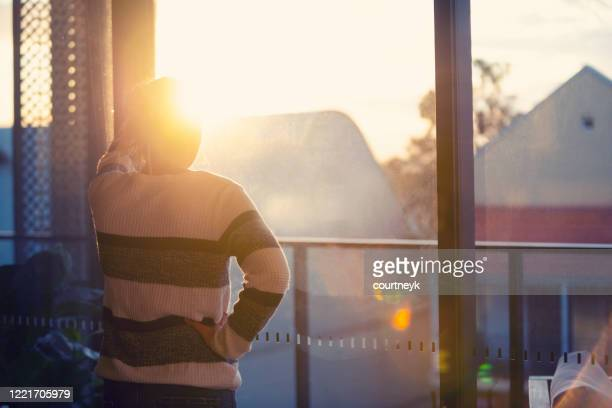 woman looking through the window at sunset. - sulking stock pictures, royalty-free photos & images