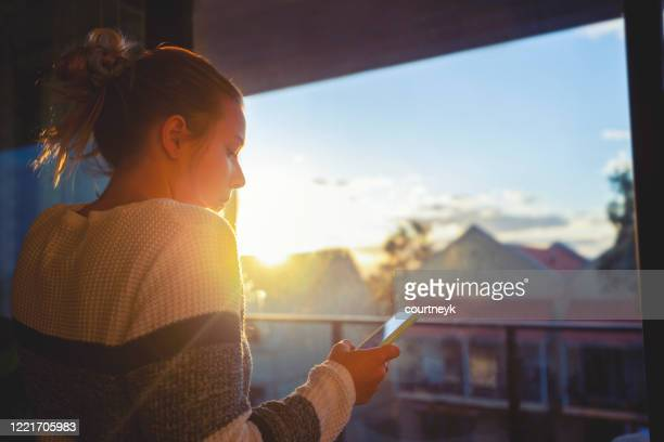 woman looking through the window at sunset. - coronavirus australia stock pictures, royalty-free photos & images