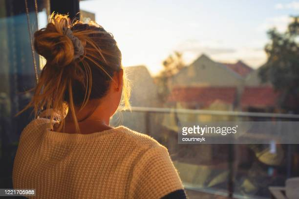 woman looking through the window at sunset. - millennial generation stock pictures, royalty-free photos & images