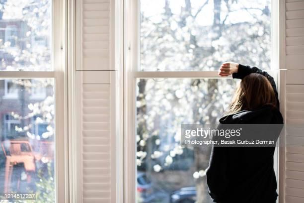 a woman looking through the window... social distancing. - atrapado conceptos fotografías e imágenes de stock