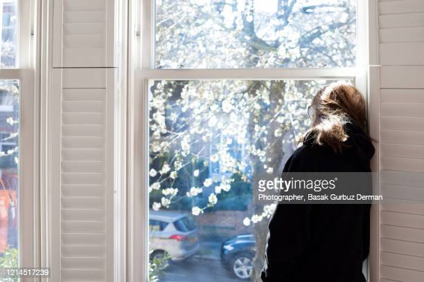 a woman looking through the window... social distancing. - trapped stock pictures, royalty-free photos & images