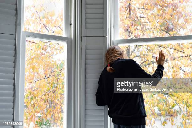 a woman looking through the window... social distancing. - waving stock pictures, royalty-free photos & images