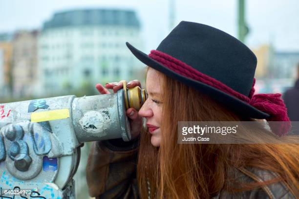 Woman looking through tourist telescope in the city