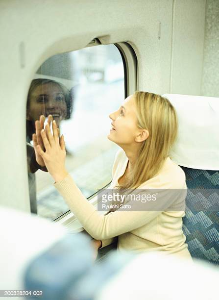 Woman looking through train window, smiling, elevated view