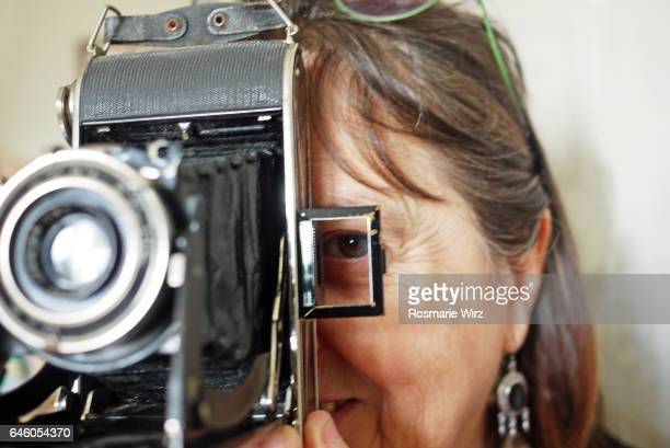 Woman looking through view finder of vintage camera
