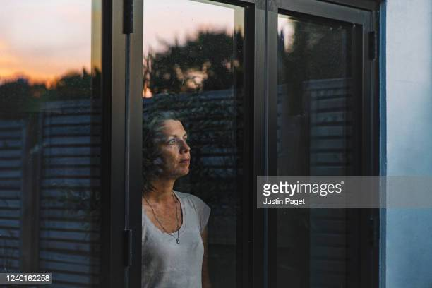 woman looking through window at dusk - boredom stock pictures, royalty-free photos & images