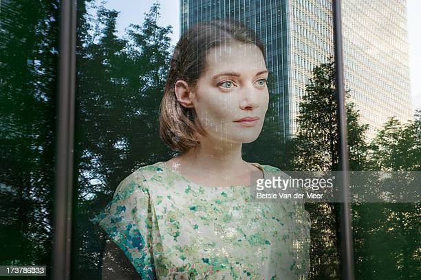 Woman looking through window  at trees and city.