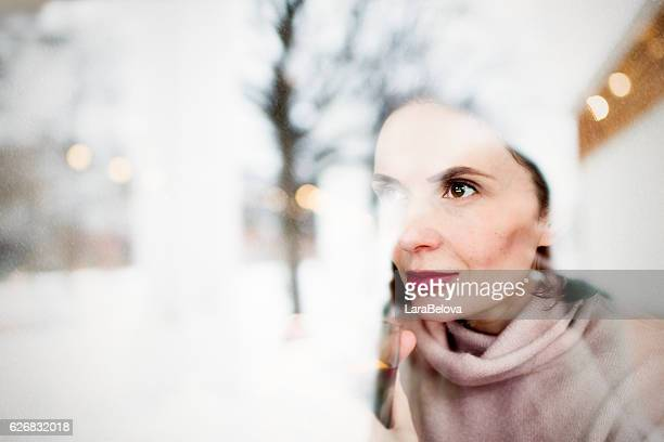 Woman looking through window at winter garden