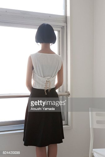 woman looking through window back view ストックフォト getty images