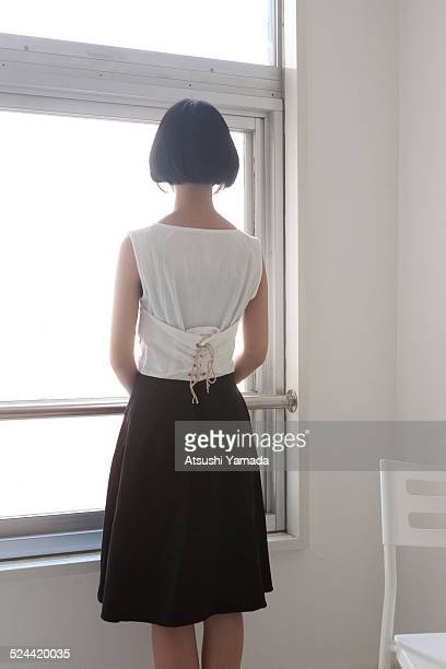 Woman looking through window, back view