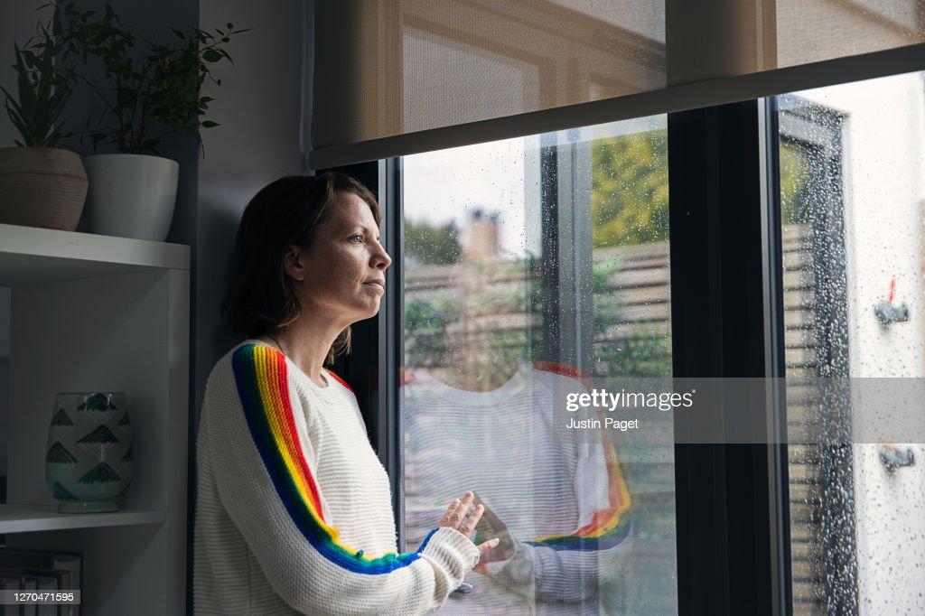 Woman looking through window hopefully : Stockfoto