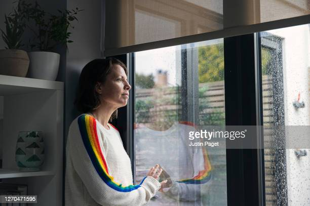 woman looking through window hopefully - contemplation stock pictures, royalty-free photos & images
