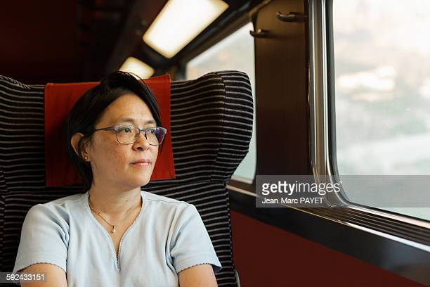 woman looking through window in a train - jean marc payet stock pictures, royalty-free photos & images