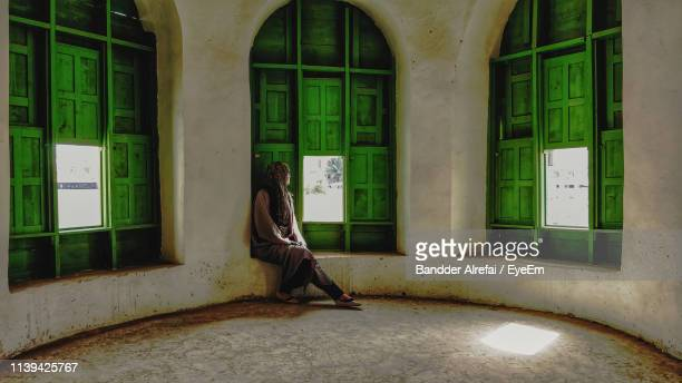 woman looking through window in building - jiddah stock pictures, royalty-free photos & images