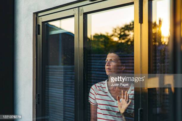 woman looking through window - negative emotion - illness prevention stock pictures, royalty-free photos & images