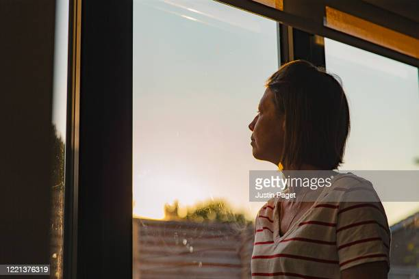 woman looking through window - negative emotion - ongerust stockfoto's en -beelden