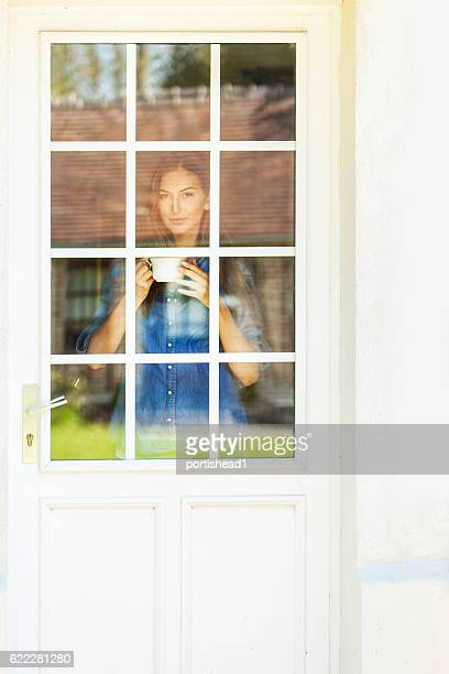 Woman looking through window of french door and drinking coffee