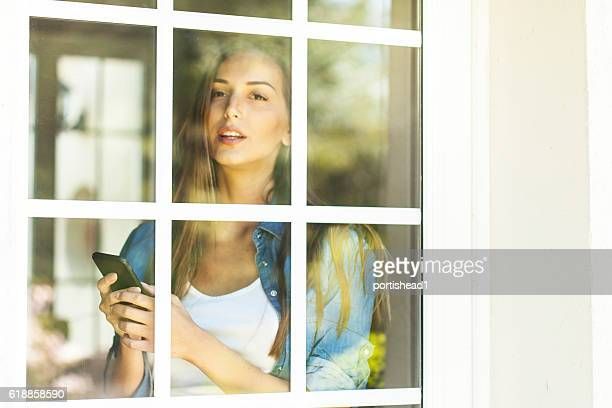 Woman looking through window of french door and using phone