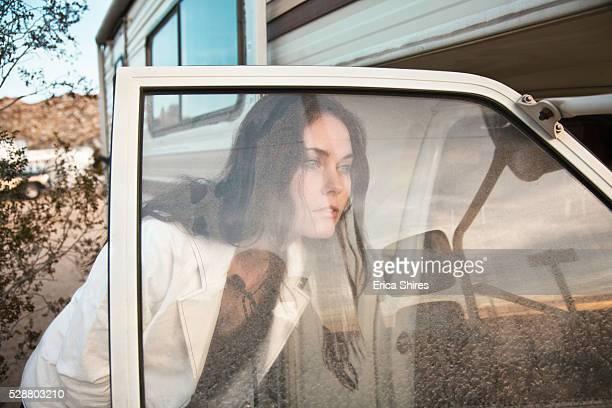 Woman looking through window of open camper door at sunset