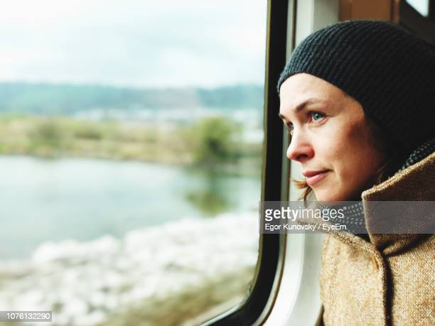 woman looking through window of train - ireland stock pictures, royalty-free photos & images
