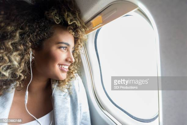 Woman looking through window on airplane