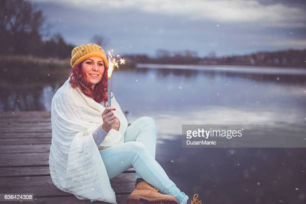 Woman looking to the lake,holding sparkles