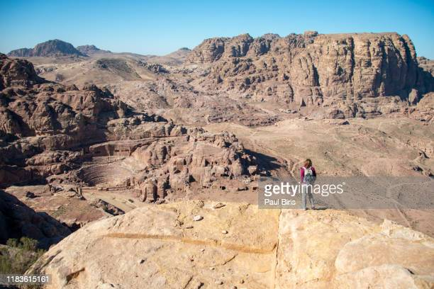 woman looking to the nabatean theatre in  petra valley, jordan - jordan middle east stock pictures, royalty-free photos & images