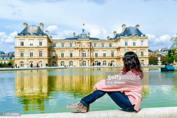 woman looking towards the luxembourg palace in the luxembourg gardens, paris - ile de france stock pictures, royalty-free photos & images