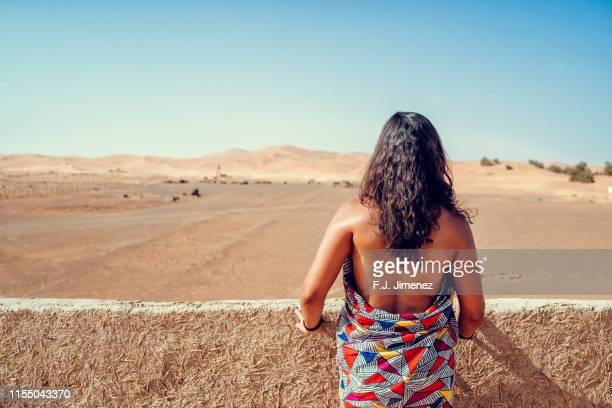 woman looking towards the sahara desert - femme touareg photos et images de collection
