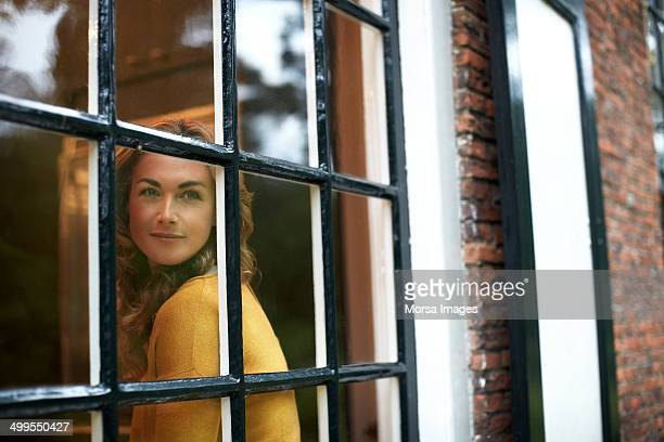 Woman looking trough cottage window