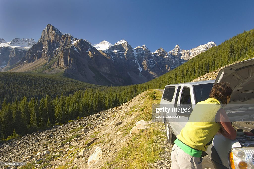 Woman looking under car bonnet, Banff National Park, Alberta, Canada : Stock Photo