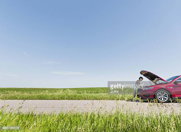 woman looking under hood of broken down car - bad luck stock pictures, royalty-free photos & images