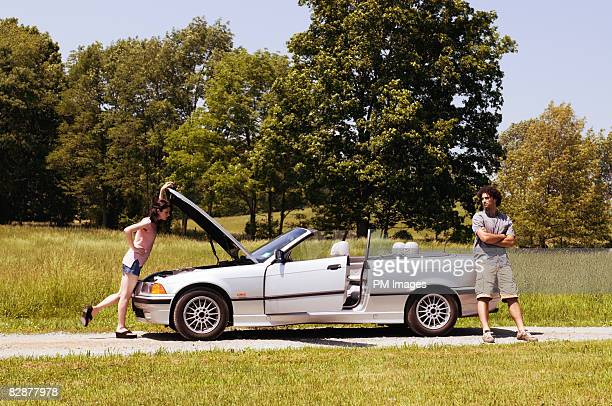 Woman looking under hood of car, man standing at r