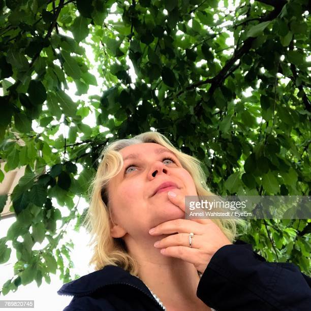 Woman Looking Up Against Tree