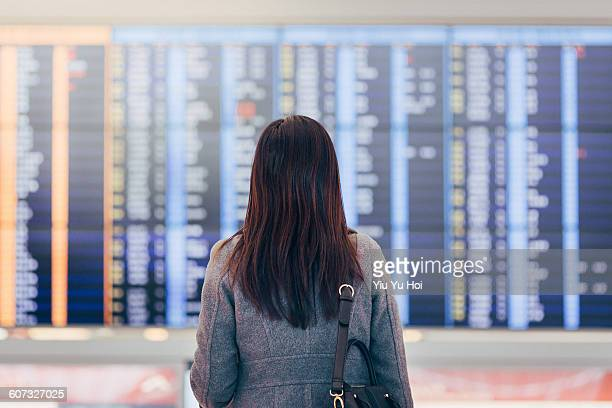 Woman looking up and checking schedule at airport