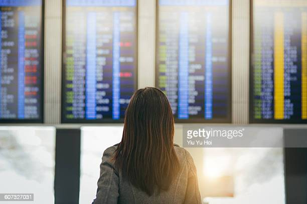 Woman looking up and checking schedule in airport