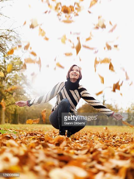 A woman looking up as autumn leaves fall