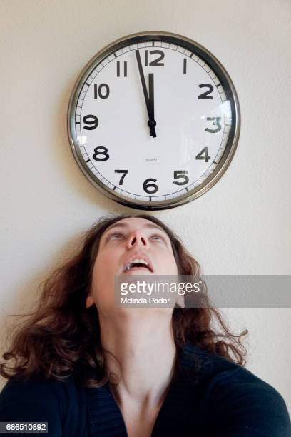 woman looking up at a clock, close to noon - time management stock photos and pictures