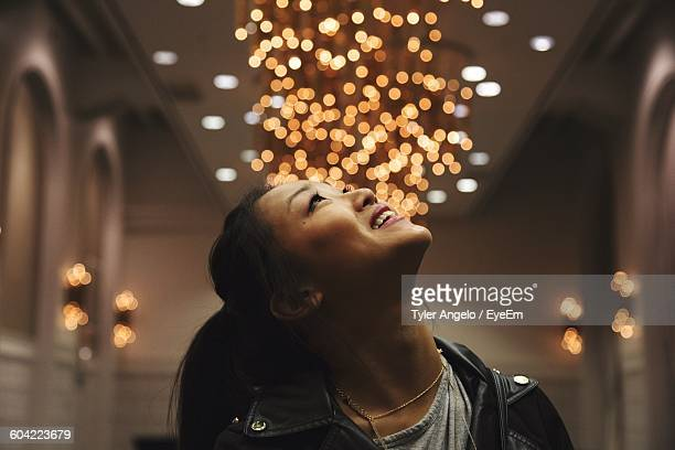 Woman Looking Up At Illuminated Decoration In Home