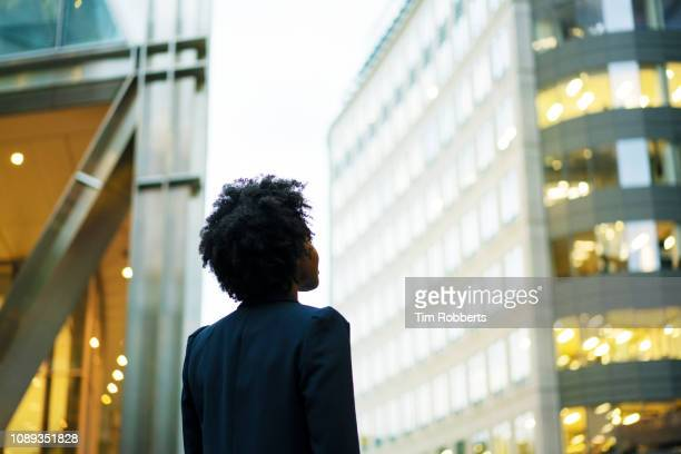 woman looking up at office buildings - anticipation stock pictures, royalty-free photos & images