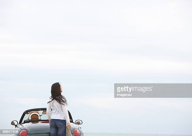 A woman looking up at sky near convertible
