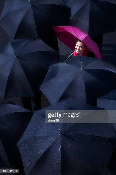 Woman looking up at sun breaking through the rain