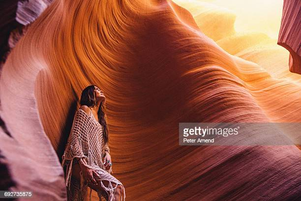 Woman looking up at sunlight in cave, Antelope Canyon, Page, Arizona, USA