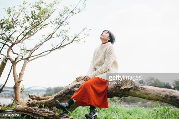 a woman looking up at the sky - 見上げる ストックフォトと画像
